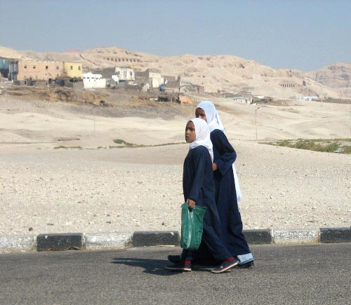 Young girls walking in a village in Upper Egypt. The Temple of Hatsheput can be seen in the background, 2007